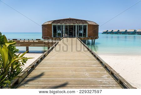 Wooden Jetty And Turquoise Indian Ocean In Exotic Maldives