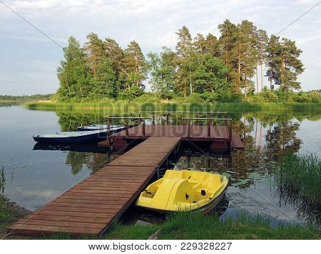 Pier, Pontoon On The Lake With Boats And A Catamaran. Rest On The Lake, In The Forest.