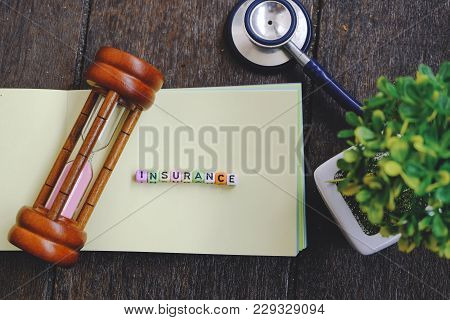 Risk Management Concept Word Block Insurance On Yellow Book Over Wooden Background