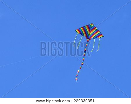 The Kite Of Iridescent Colors Hovers In The Blue Sky. Toy Of Joyful Childhood. Cloudless Mood. Dream