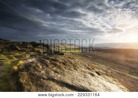 Hikers In Stunning Peak District Landscape During Autumn Sunset