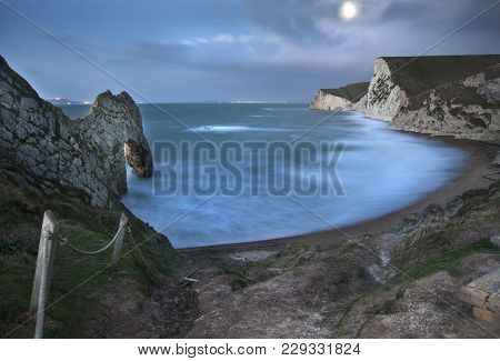 Beautiful Landscape Image Of Durdle Door On The Jurassic Coast In Pre-dawn Moonlight
