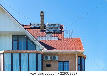Solar Battery On A Burgundy Roof Of A Private House