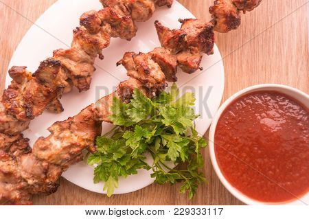 Mutton Shish Kebabs On Two Skewers On The Plate With Tomato Sauce And Parsley On Wooden Table