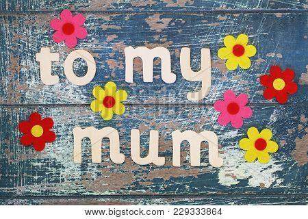 To My Mum Written With Wooden Letters On Rustic Surface With Colorful Flowers