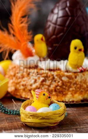a toy chick and some eggs in a nest, and a mona de pascua, a cake eaten in Spain on Easter Monday, topped with a chocolate egg, some feathers and some toy chicks, placed on a rustic wooden table