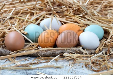 Natural Raw Eggs Resting On Straw And Burlap With White Rustic Wood