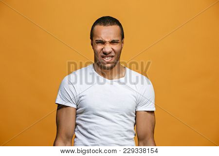 Young Man With Disgusted Expression Repulsing Something, Isolated On The Orange