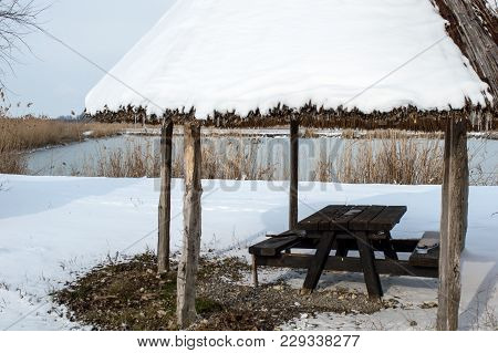 Benches And Table/ Resting Place Next To A Frozen Fishpond. Cold Snowing Winter Day In The Resting P