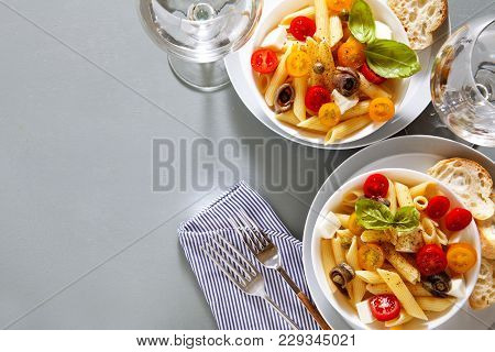 Healthy Summer Light Pasta Salad With Fresh Raw Tomatoes, Anchovies And Capers. Glasses With Water