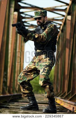 The Soldier In Military Uniform Is Standing On The Railway Bridge And Aiming With Pistol.