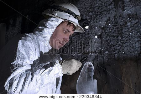 Cave Explorer Carefully Examines The Structure Of The Ice Formations Through A Magnifying Glass