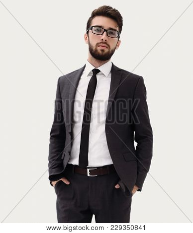 Young businessman standing with hands in pockets.