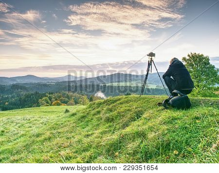 Long Hair Woman Photographer Stand On Meadow And Wait For Sunrise. Short  Grass And  Misty And Light