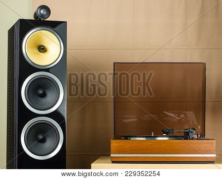 Vintage Turntable Playing A Vinyl Record And Modern Black Speakers