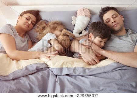 Family sleeping in bed at home