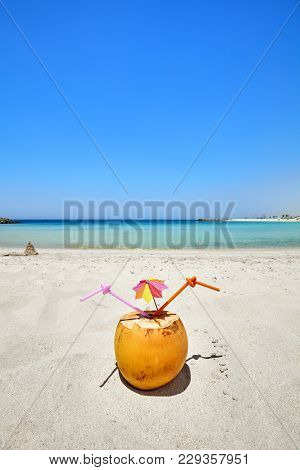 Coconut cocktail with colorful umbrella and two straws on a beach, summer holiday concept, selective focus.