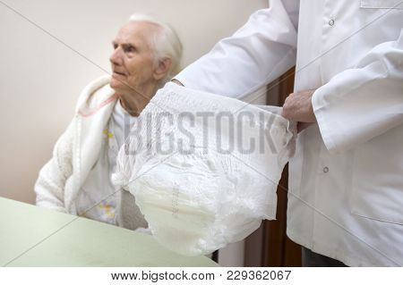The Nurse Shows Diaper Pants For Old People. An Old Woman In A White Bathrobe And Nightgown Sits On