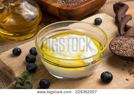 Cottage Cheese With Flax Seed Oil In A Bowl, With Flax Seeds And Blueberries In The Background