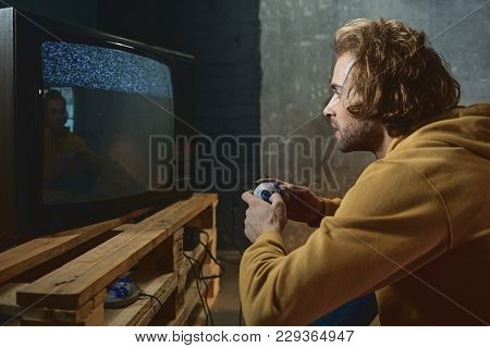 Side View Interested Bearded Male Typing In Joystick While Looking At Display Of Retro Television Se