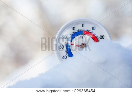 Thermometer with celsius scale placed in a fresh snow showing sub-zero temperature minus 25 degree - extreme cold winter weather concept