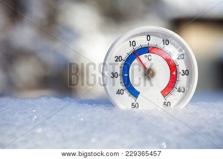 Thermometer with celsius scale placed in a fresh snow showing sub-zero temperature minus 10 degree - cold winter weather concept