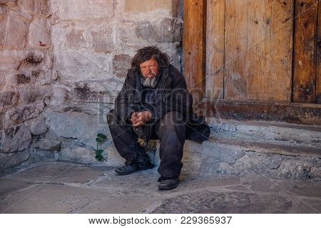 Arkhyz, Karachay-cherkessia, Russia - April 26, 2017: Shabby Homeless Sad Old Man Is Sitting On The