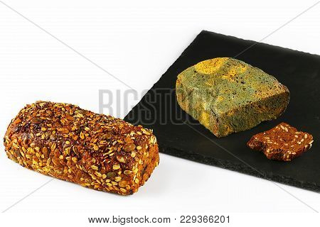 Half A Loaf Of Mouldy Rye Bread And Fresh Grain Bread, On A Black Shale Board Isolated On White Back