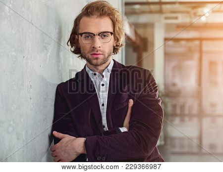 Confident Unshaven Smart Male Leaning Against Wall While Standing In Apartment. Self-confidence Conc