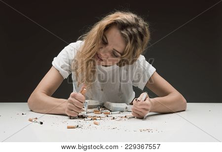 Wrathful Female Holding Cigarettes In Her Hands And Smashing Them With Anger. Isolated On Background