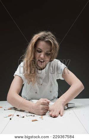 Waist Up Portrait Of Discontented Female Sitting At Table And Smashing Cigarettes With Fist. Isolate
