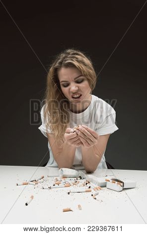 Waist Up Portrait Of Furious Female Smashing Cigarettes, Her Face Expressing Anger. Isolated On Back