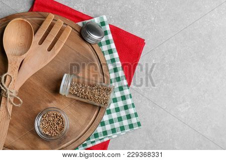 Wooden cooking utensils, napkins, and spice on gray background, top view