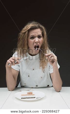 Waist Up Portrait Of Miserable Girl Sitting In Front Of Plate Full Of Cigarettes And Putting Into He