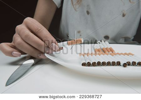 Harm Concept. Close Up Of Female Hand Holding Scratchy Ciggy Above Plate. Isolated On Background