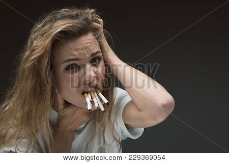 Portrait Of Depressed Woman Holding Many Ciggies With Her Teeth And Looking At Camera With Disgust.