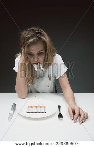 Sad Young Girl Sitting At The Table And Chewing Cigarettes. She Is Looking At Plate With Nicotine In