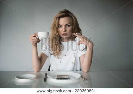 Portrait Of Serious Girl Holding Mug In One Hand And Cellphone With Ciggy In Another. She Is Sitting