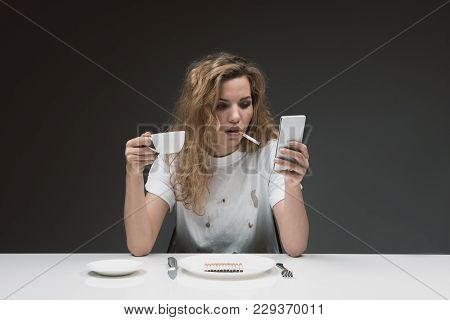 Portrait Of Serene Girl Smoking While Relaxing With Mobile Phone And Mug In Hands. Plate With Cigare