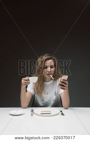 Portrait Of Tranquil Woman Sitting At The Table With Ciggy In Mouth. She Is Holding Cup And Smartpho