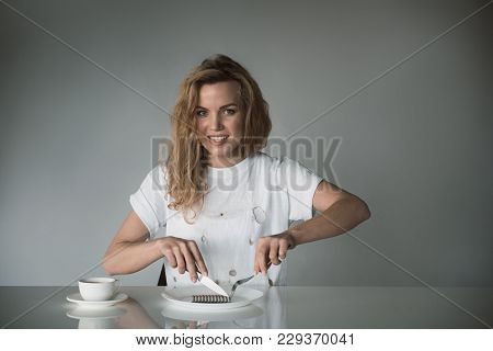 Waist Up Portrait Of Smiling Girl Relaxing At The Table And Using Cutlery For Eating Cigarettes. Iso