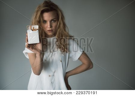 Waist Up Portrait Of Upset Woman Showing Package With Tobacco. Focus On Smoke. Copy Space In Right S