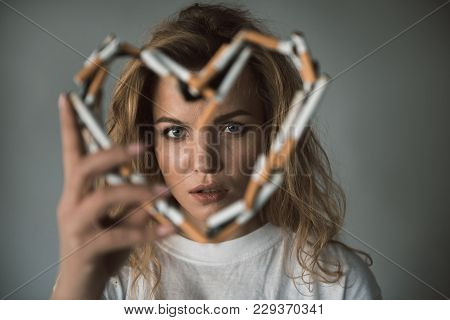 Portrait Of Quiet Lady Looking Through Heart Made Of Cigarettes. Focus On Face. Isolated On Backgrou