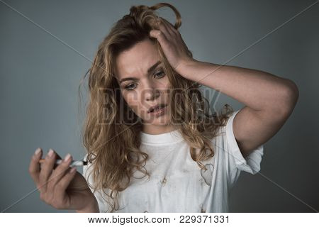 Portrait Of Unhappy Female Smoker Holding Cigarette In One Hand And Touching Hair With Another. Isol