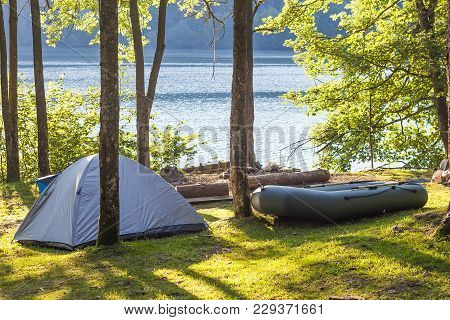 Camping Tent And A Boat In Green Forest On The Bank Of A Lake