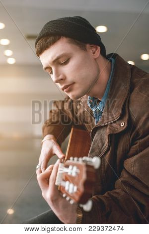 Portrait Of Satisfied Man Playing Guitar In Apartment. Melody Concept