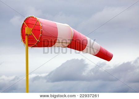 A windsock inflated by the wind against a cloudy sky.