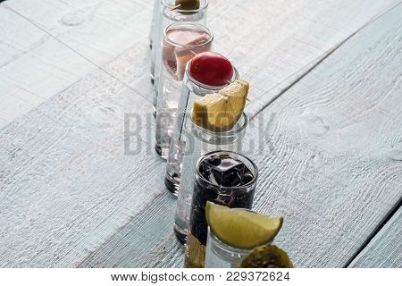 Shots With Alcohol On A Wooden Cover. Inside The Ice Cubes. On Each Shot, On Top Of That Lies - Radi