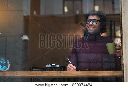 Portrait Of Happy Guy Making Notes In His Notepad. He Is Drinking Cup Of Tea And Smiling. Inspiratio