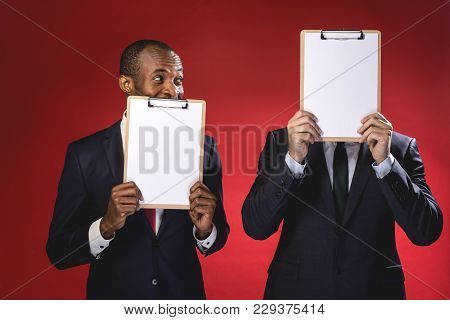 Find Your Partner. Cheerful Pleasant Young Men Are Holding Sheets Of Paper And Hiding Behind Them Wh